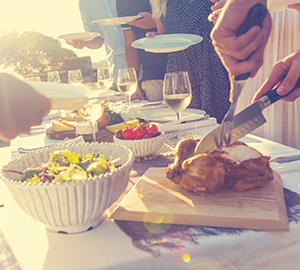 Carving a chicken with friends and family. There is a long table and everyone is standing with plates waiting to be served. There is salad, wine and cheese on the table.