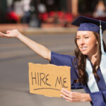 graduate-with-hire-me-sign-508629964-300x270
